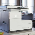 HP PageWide Pro 477dw MFP sitting on a desk in an office.