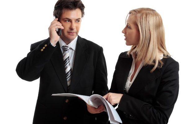Business people discuss or make enquires or decision regarding a report, contract or other document.