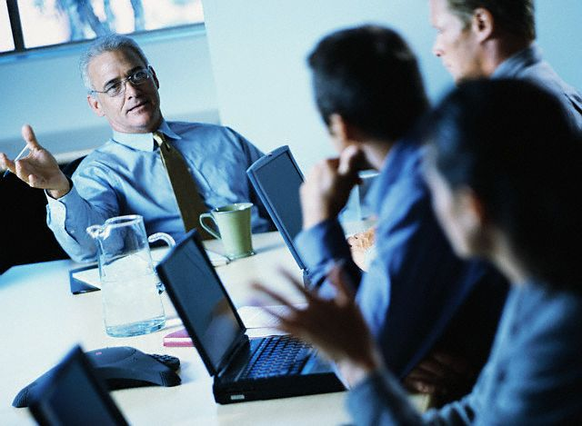 Businesspeople Using Laptops During Meeting