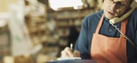 Clerk writing on clipboard in store